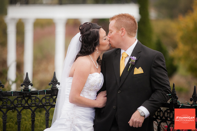 bride and groom kissing in front of rod iron fence