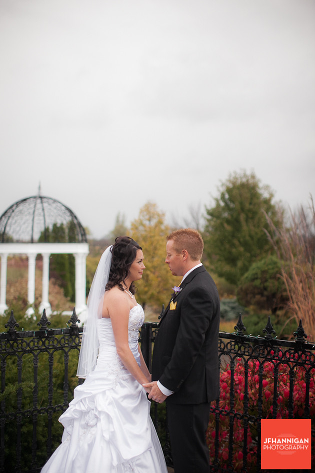 bride and groom in front of rod iron fence fall colors in background