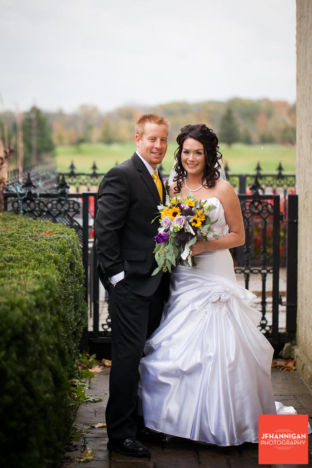 bride and groom with rod iron fence and fall folliage in background