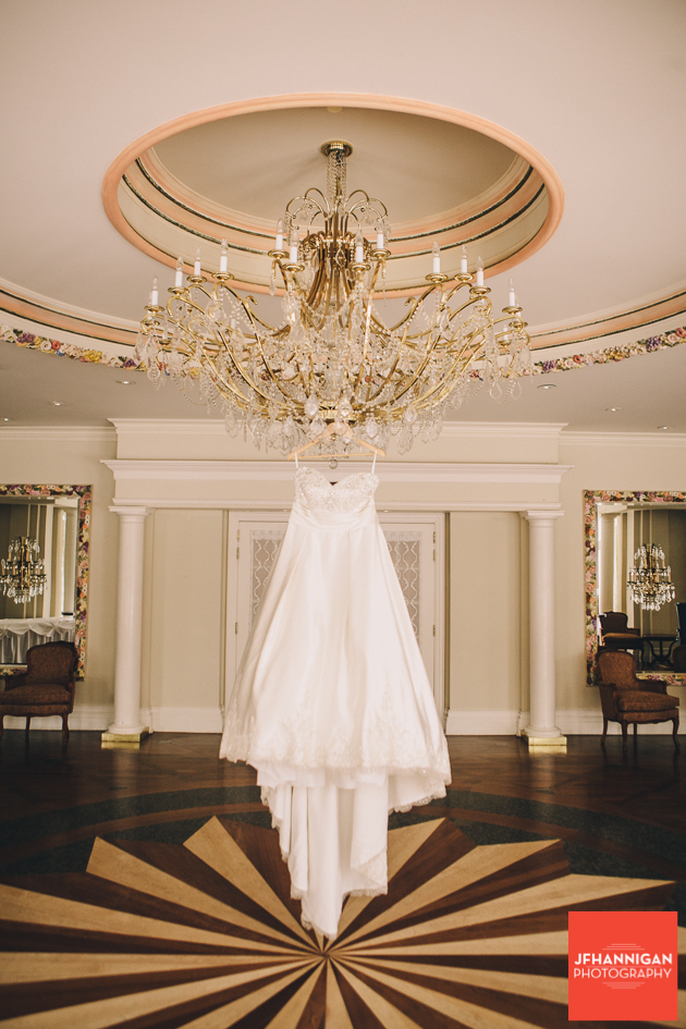 bridal gown hangs from candeliers