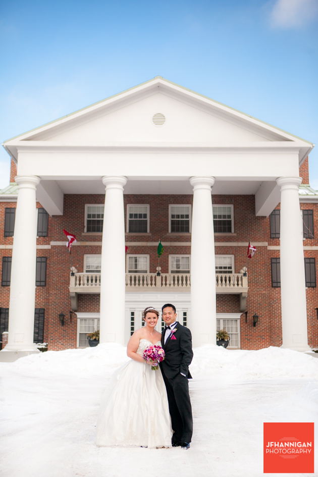 bride and groom in snow in front of Queen's Landing