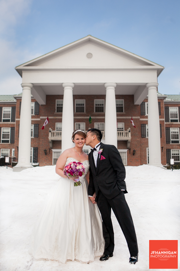 groom kisses bride's cheek while standing in snow