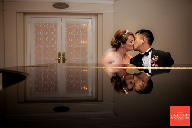 bride and groom kissing while sitting at grand piano
