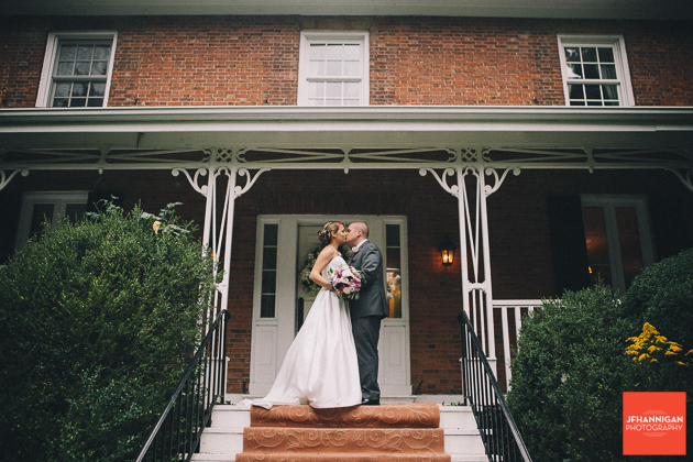 bride and groom kissing on front porch