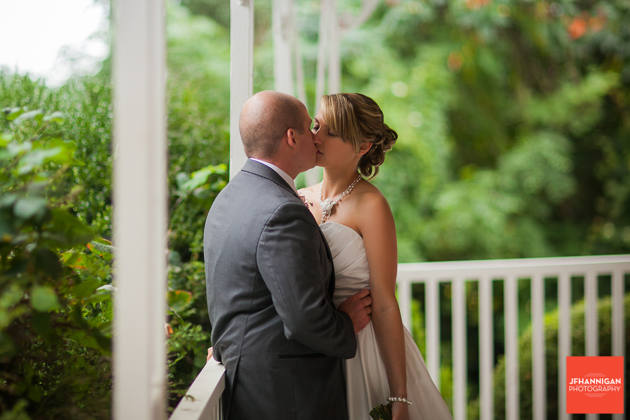 bride and groom kissing on front porch white railing and green foliage