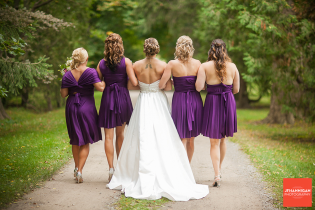 backs of bridal party as they walk down raod