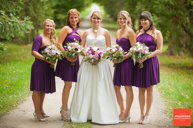 bridal party in purple standing on road