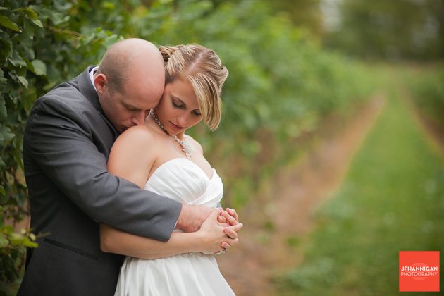 groom kissing bride's shoulder in vineyard