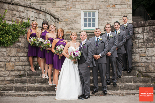 wedding party standing in V formation on steps cut stone buidling in background