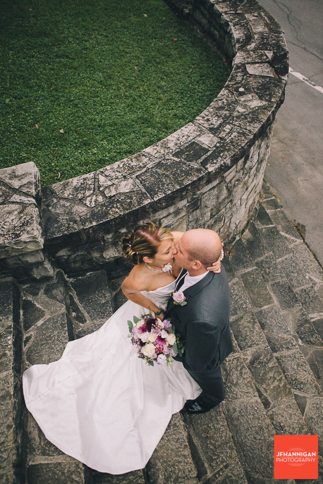 bride and groom kissing on cut stone staircase