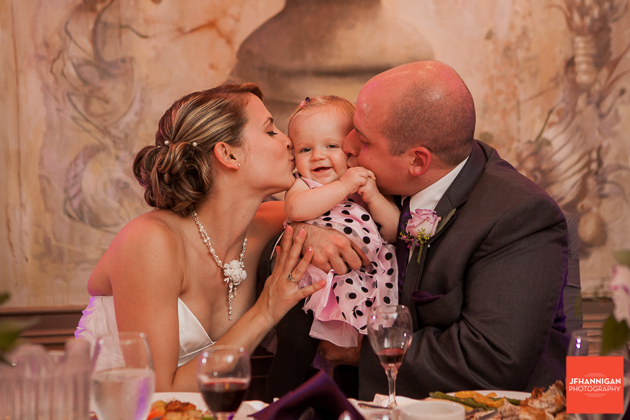 bride and groom kissing toddler at reception