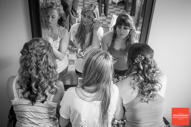 bride and bridesmaids in mirror putting on make-up