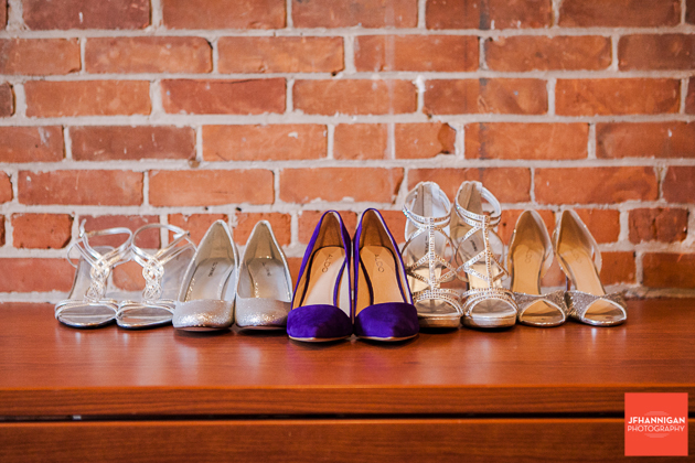 bride and bridesmaid's shoes on ledge with brick wall behind