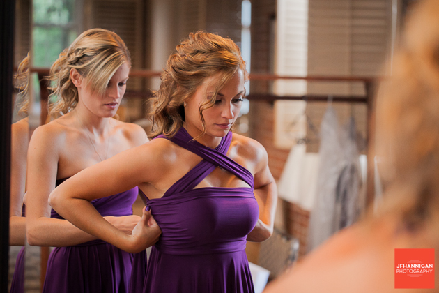 bridesmaides putting on purple dresses