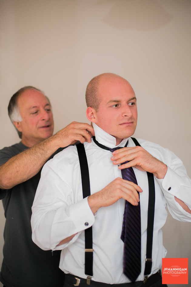 groom putting on tie