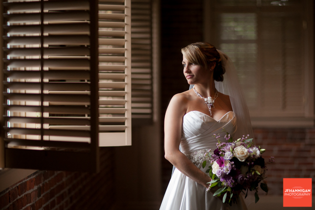 bridal portrait gazing out window with shutters