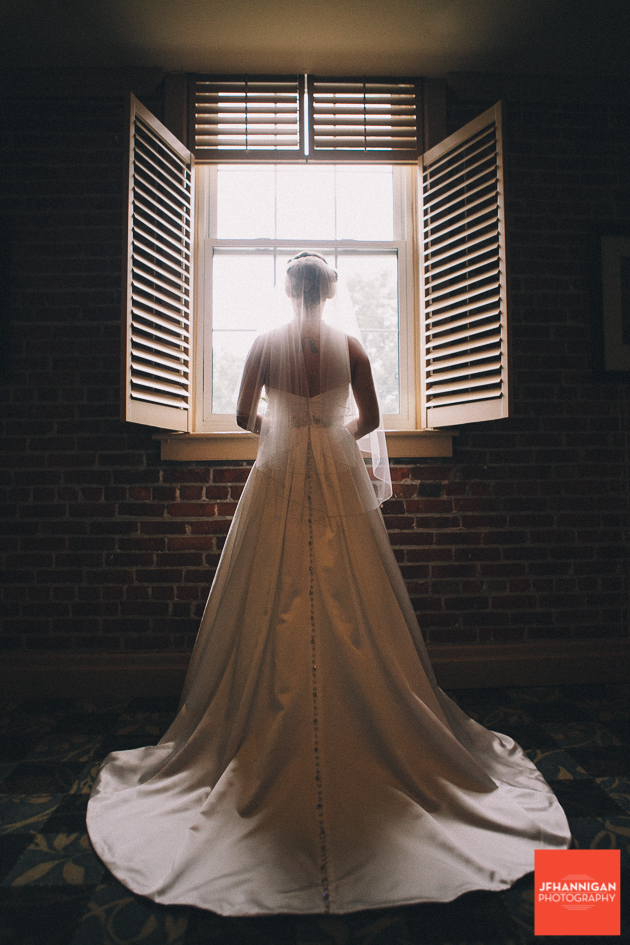 bride looking out window showing back of gown with train