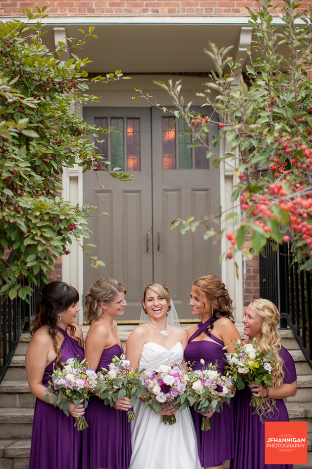 bridal party in purple with entrace and greenery in background