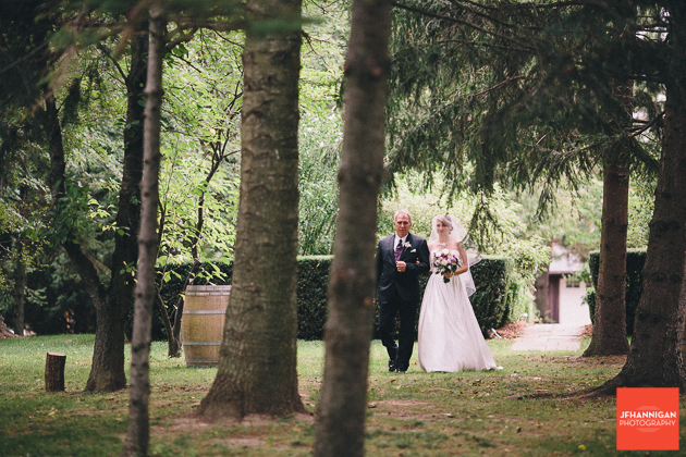 bride and father through trees at outdoor wedding