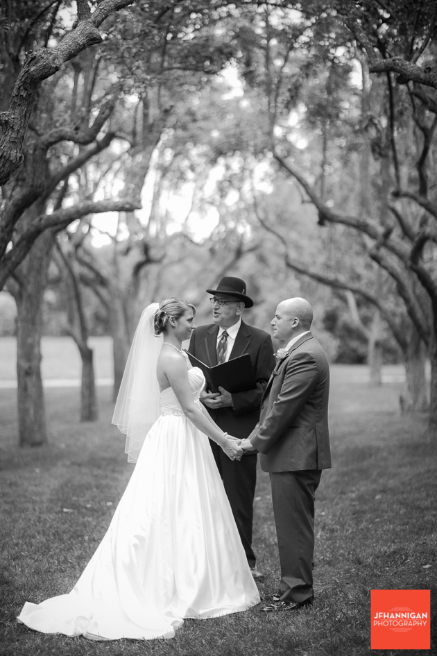 bride and groom hold hands under trees with wedding official  in background