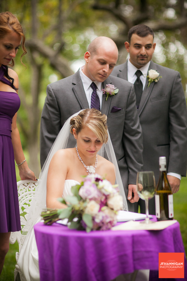 bride signs marriage register while other watch purple accents