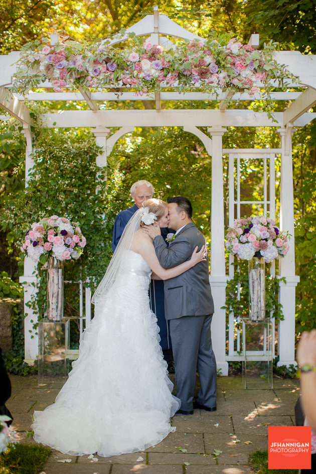 wedding kiss under trellas decorated with pink and mauve flowers