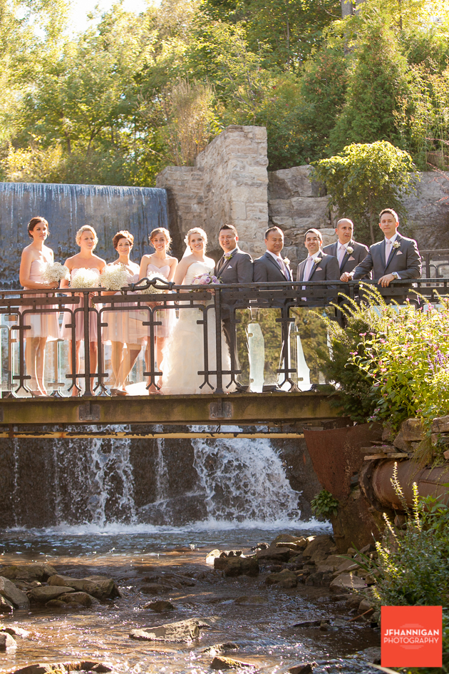 wedding party on bridge with waterfalls in background