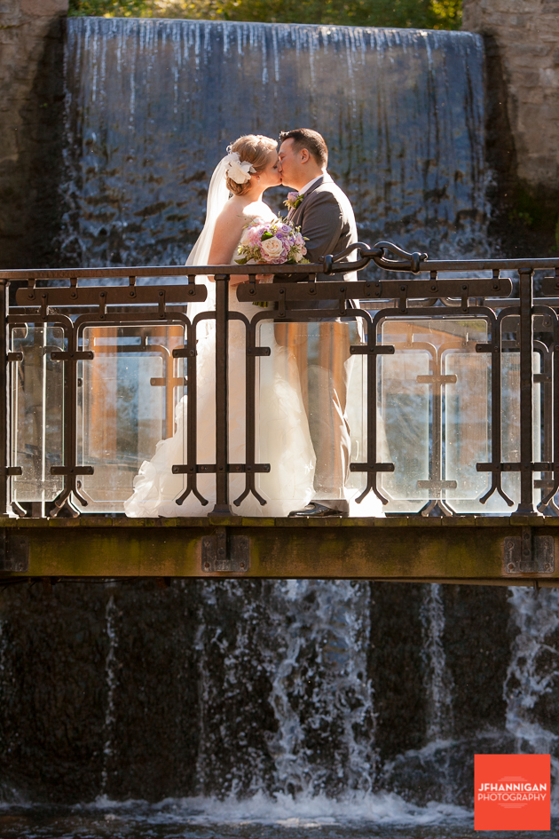 bride and groom kissing on bridge waterfalls in background