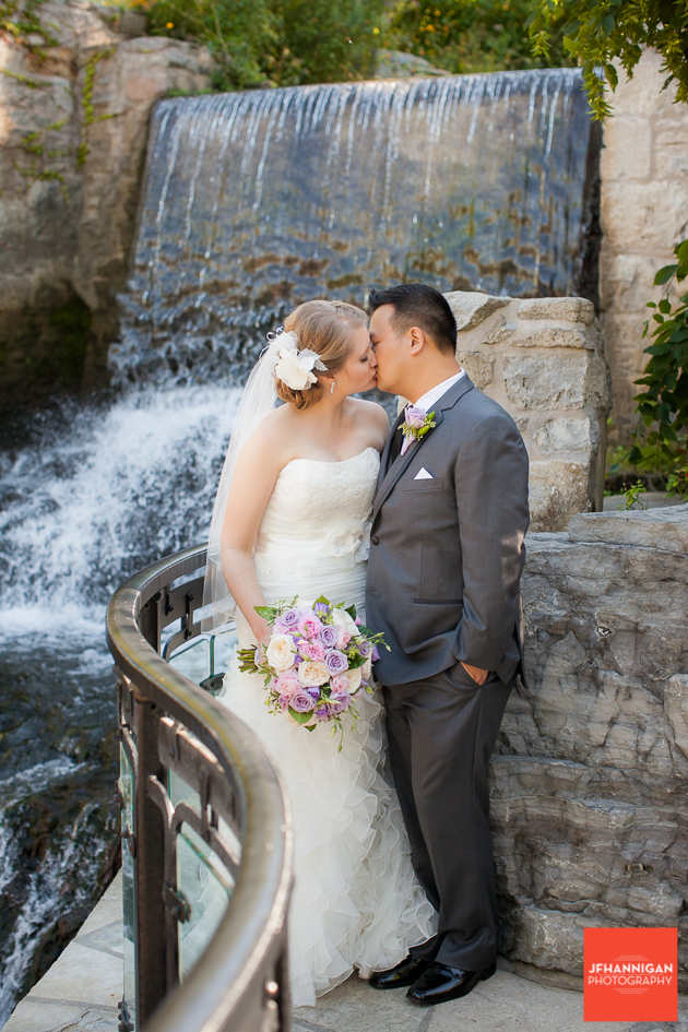 bride and groom kissing by waterfalls at Ancaster Mill