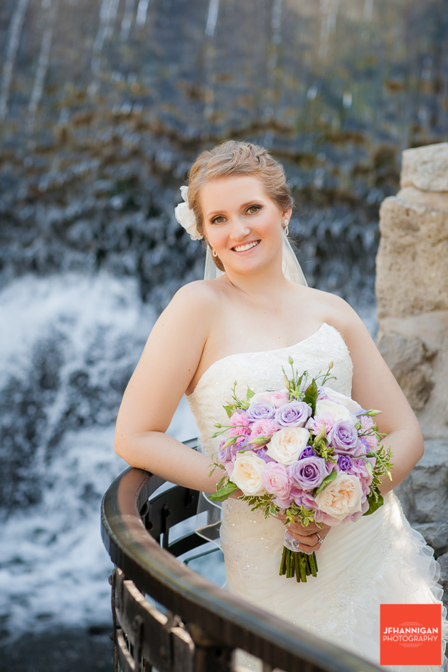 bride with pink and mauve rose bouquet with waterfalls in background