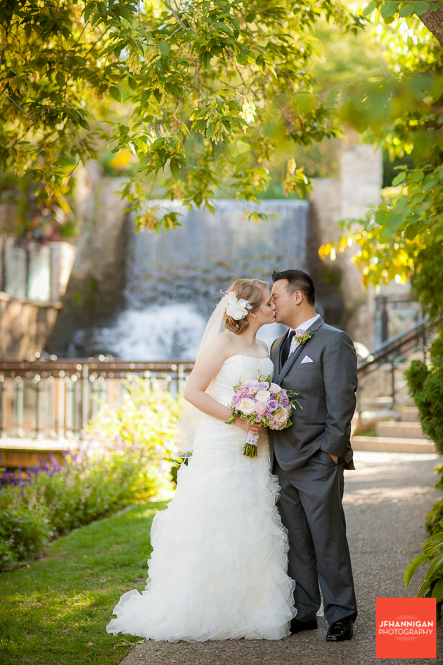 bride and groom kissing on pathway with waterfalls in background Ancaster Mill