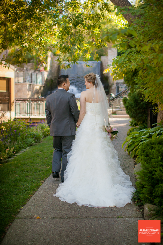 bride and groom walking path to waterfalls at Ancaster Mill