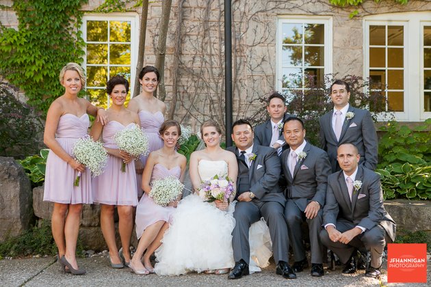 wedding party in mauve and gray with cut stone building in background