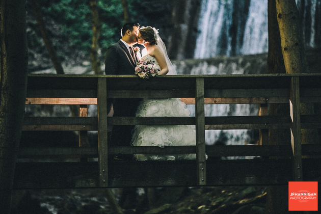 bride and groom kissing on bridge in wooded area with waterfalls in background