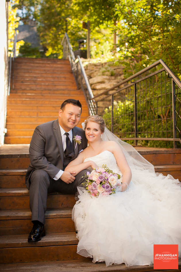 bride and groom sitting wooden staircase with green foliage in background
