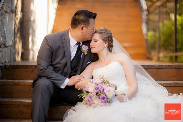groom kisses bride's forehead while sitting on wooden staircase