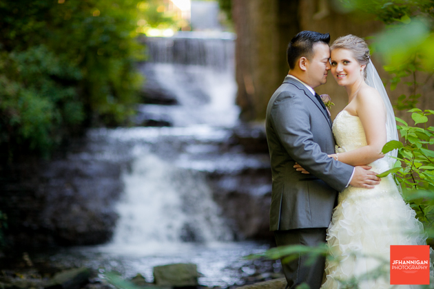 bride and groom beside waterfalls at Ancaster Mill Niagara Wedding Photographer