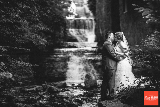 black and white photo of bride and groom kissing by waterfalls