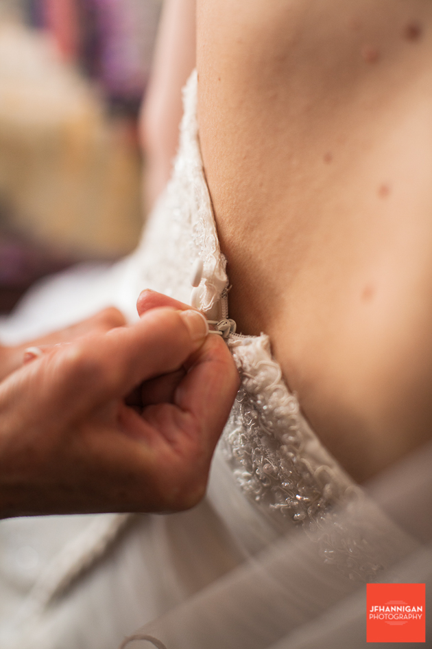 doing up zipper on bridal gown