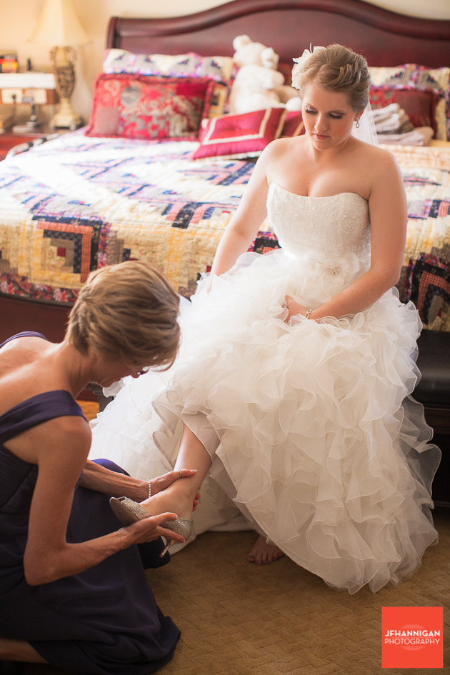 mother puts on bride's shoes