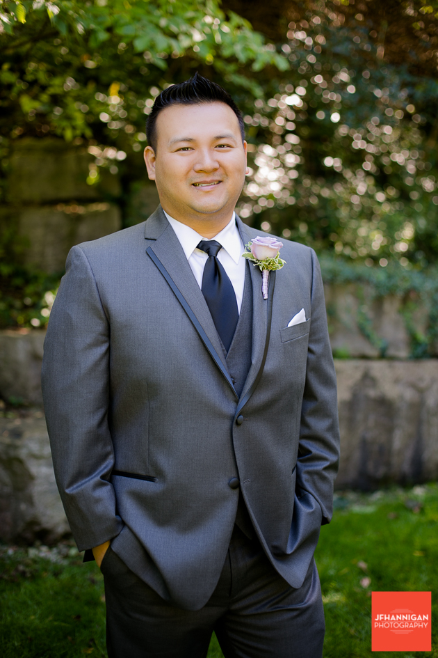 groom in gray suit with mauve rose boutineer