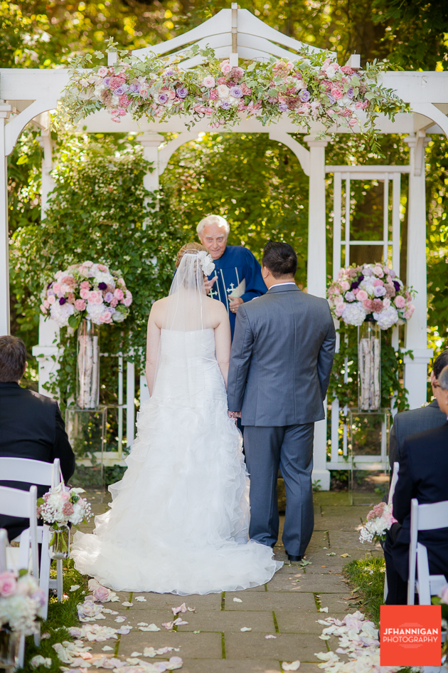 bride and groom under wedding gazebo