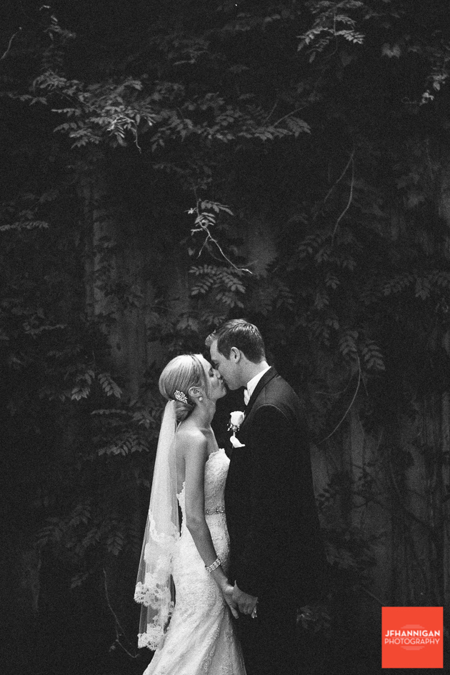 black and white photo with bride and groom kissing