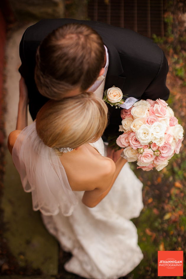 overhead photo of bride and groom showing rose bouquet and boutineer