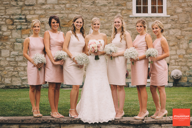 bride and bridesmaids in front of stone building