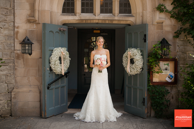 bride in church entrance decorated with baby's breath wreath