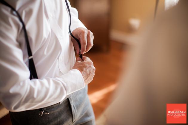 groomsman putting on suspenders