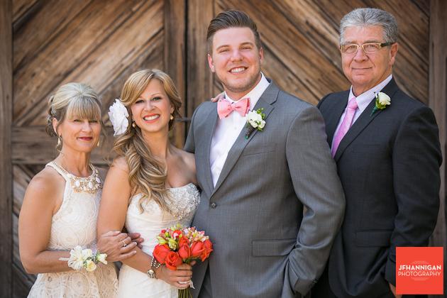 bride and groom with bride's parents in front of barn door