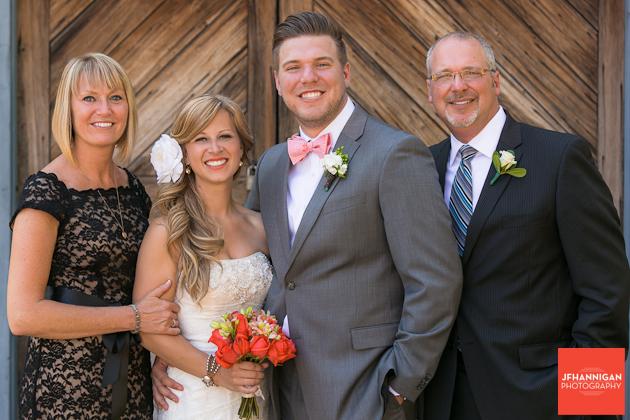 bride and groom with groom's parents in front of wood door