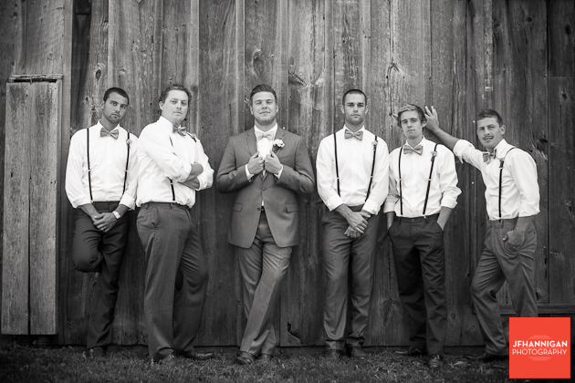 groom and groomsmen in standing at side of barn